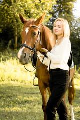 Молодая девушка со светлыми волосами стоит рядом с коричневой лошадью