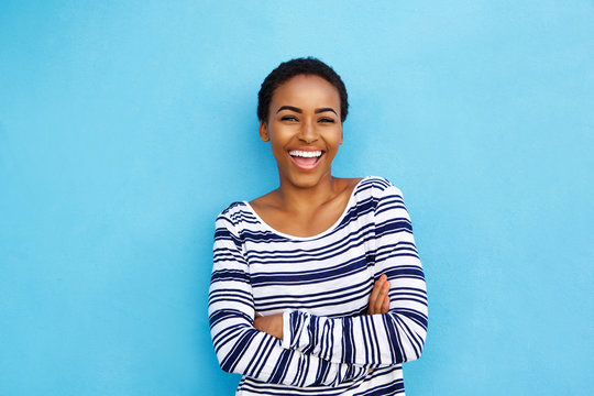 happy young black woman laughing against blue wall