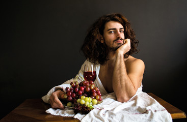 Photo of handsome guy with long curly hair at the table with glass of red drink and a plate of grapes