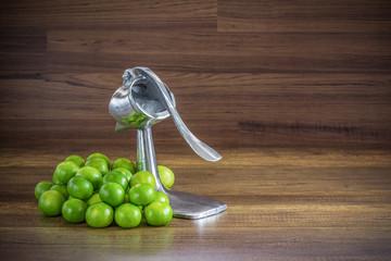 stack of green lemon with aluminum manual juicer squeezer fruit