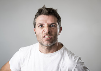 young attractive man with blue eyes looking angry and mad in rage emotion and upset