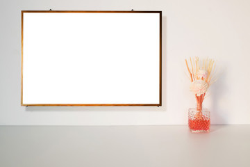 Blank board or white board on the wall with fake flowers on the table.