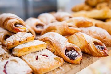 Keuken foto achterwand Bakkerij Close up freshly baked pastry goods on display in bakery shop. Selective focus