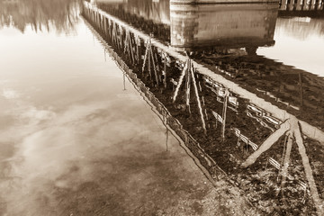 Iron bridge for trains, pedestrians and cars, reflected in water, river Ticino, between Sesto Calende and Castelletto Ticino, Italy. Vintage tone, sepia color
