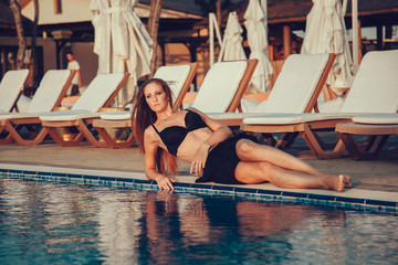 fashion photo of beautiful tanned woman with red hair in elegant black bikini relaxing beside a swimming pool