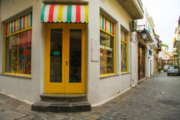 Traditional multicolor facade of shop from the street greek island town panorama