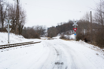 Railroad crossing along a snow covered country road, in a rural