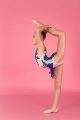 Teenage girl in blue dress doing gymnastic exercises on pink background.