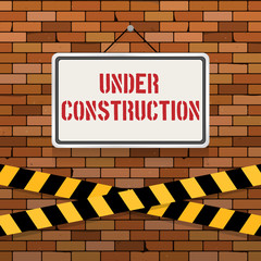 Simple white sign with text 'Under Construction' hanging on a red brick wall with warning tapes. Grunge brickwork background. Building, engineering concept. Creative template for web design