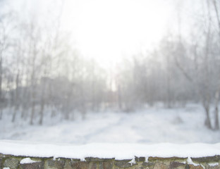 Blurred winter forest background in snow. Old stone fence on the foreground