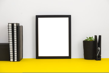 Empty picture frame on yellow book shelf. Home decor mock up.