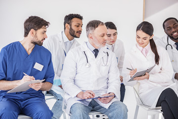 Cheerful physician telling with partners in clinic