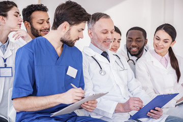Cheerful doctors watching at tablet of colleague