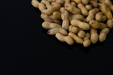 Pile of peanuts with shell isolated on black background
