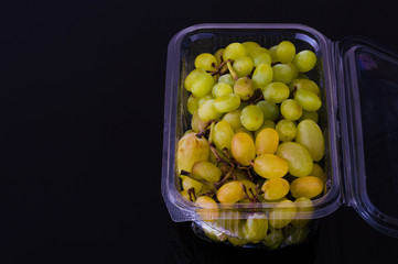 Bunch of fresh grapes in plastic cup on black background