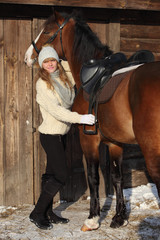 Country girl with beautiful saddle horse standing in the stable door