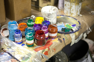 Multi colored paints in jars for drawing. Color paints for creativity on a white background. Boxes with paints on a table.