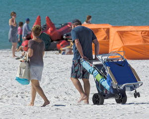 Beach goers hauling beach chairs and umbrella onto Clearwater Be