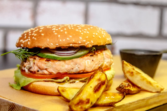 Burger with fish (salmon), cucumber and tomato.