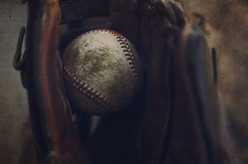 Old baseball caught in leather glove.  Sport or game background or print.