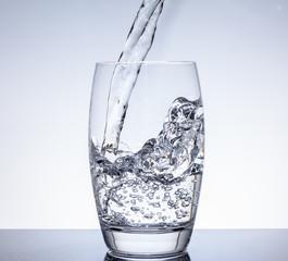 Wasser in Trinkglas einfüllen