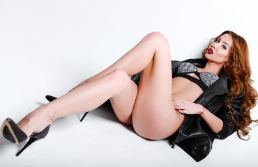 Studio fashion shot: gorgeous sexy young girl in lingerie and leather jacket lying on a floor