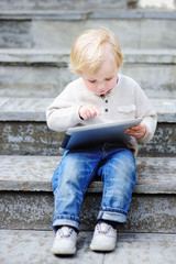 Cute blonde toddler boy playing with a digital tablet outdoors