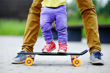 Toddler Girl Learning To Skateboard With Her Father Close Up