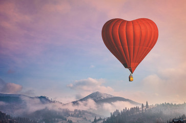 Beautiful red air balloon heart shape against blue and pink pastel sky in a sunny bright morning....