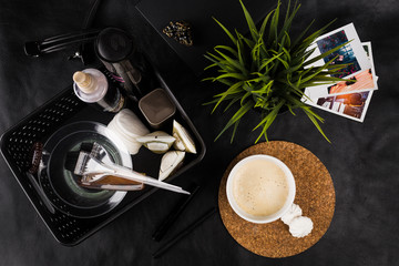 morning cup of hot coffee on the table together with creams and oils for hair care