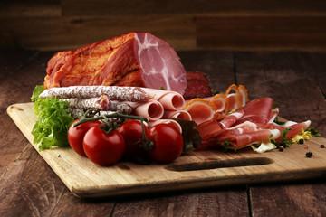 Food tray with delicious salami, pieces of sliced ham, sausage,