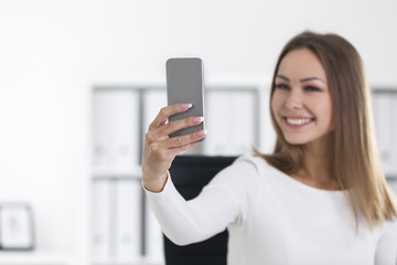 Cheerful woman in office making a selfie