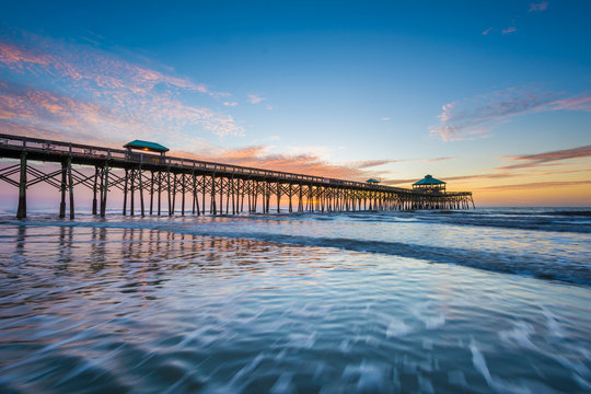 Waves in the Atlantic Ocean and the pier at sunrise, in Folly Be