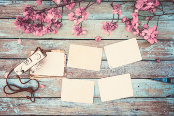 Retro camera and empty old instant paper photo album on wood table with flowers border design - concept of remembrance and nostalgia in spring. vintage style