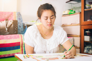 Pretty asia woman drawing a picture with color pencil in her hand. Front view on drawing girl. Smiling young woman draw a picture at home.