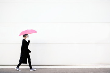 Young woman walking with pink umbrella