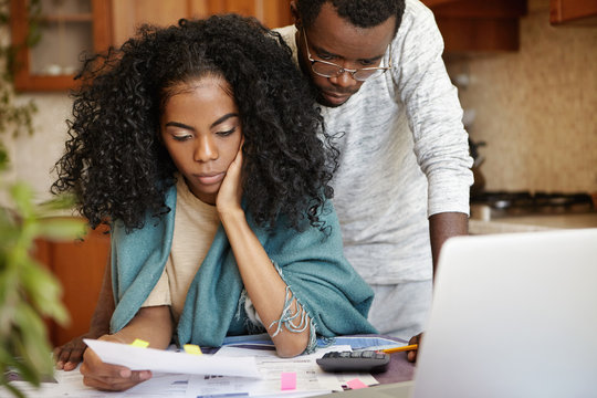 Stressed African couple having many debts trying to cut their domestic expenses to save money and pay off loan in bank. Worried wife holding piece of paper and reading notification about eviction