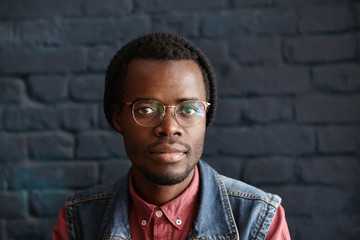 People and lifestyle concept. Headshot of attractive young unshaven dark-skinned male in trendy clothes looking at camera with serious and confident face expression, having rest indoors alone