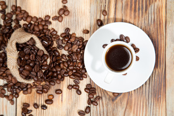 cup of coffee with grains on the wooden background