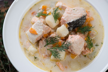 Close-up of fish soup with salmon in a white glass plate