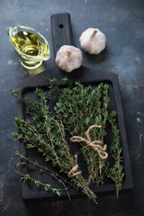 Dark wooden cutting board with fresh thyme, olive oil and garlic