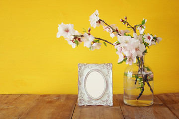 Vintage blank photo frame next to spring white flowers on wooden table