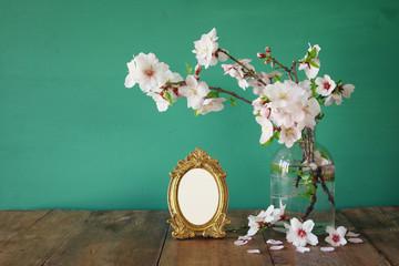 Vintage blank photo frame next to spring white flowers