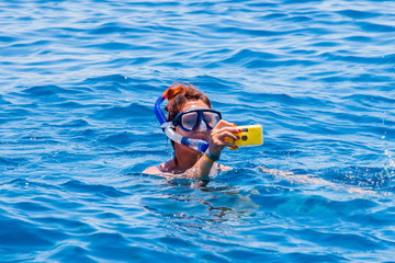 happy woman wearing a mask in the sea, along with a camera