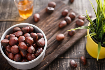 chestnuts with roasted coffee beans on wooden background.