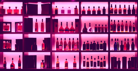 Various alcohol bottles in a bar, back light, logos removed, ton