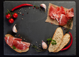 Ham , cherry tomatoes, red pepper and herbs on black stone slate board. Top view