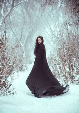 sexy  girl a demon walks alone. wearing a long, black traveling cloak. woman  gothic witch, fallen angel. Dark Queen, with aggressive face make-up. trees covered with frost, snow, winter nature