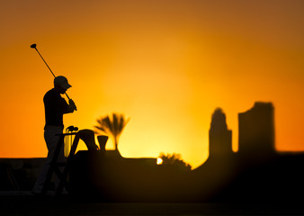 Golf player silhouette on a colorful sunset holding a golf stick. Buildings, sun and palm tree on the background.