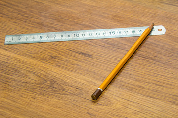 Pencil and ruler on a wooden background
